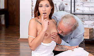 Curious old man watches a sexy brunette performing stretching exercises in the air a tight machine