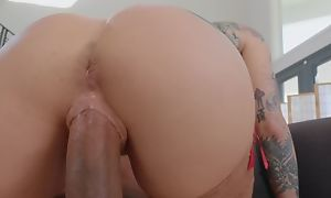 Tattooed pornstar wearing stockings fucks black dude on get under one's couch